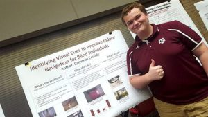 Cameron Cassidy standing in front of a research poster
