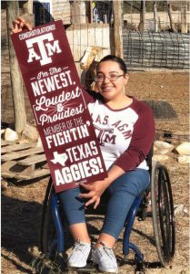 Photo: Briana Bazan, wheelchair user, hold her admissions congratulations poster